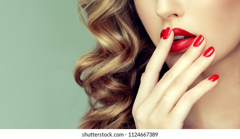 Beautiful girl with long wavy hair .  woman with red manicure .  girl with bright color nail polish on the nails . Makeup and cosmetics