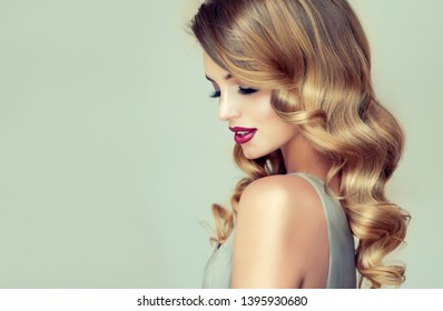 Beautiful girl with long wavy hair .  Blonde woman with curly hairstyle and red lips