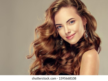 Beautiful girl and long wavy hair .  Brunette with curly hairstyle - Shutterstock ID 1595668108