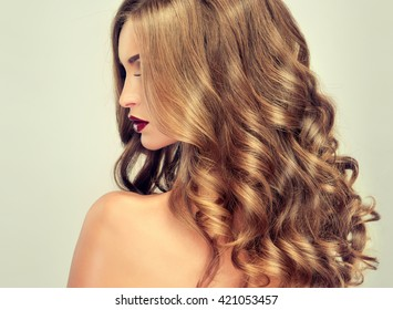 Beautiful girl with long wavy hair .  fair-haired  model  with curly hairstyle   and fashionable makeup