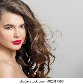 Beautiful girl with long wavy hair. Brunette with curly hairstyle. Professional Makeup. Fashion Earrings.