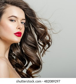 Beautiful girl with long wavy hair. Brunette with curly hairstyle. Professional Makeup.