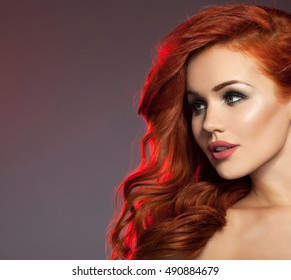 Beautiful girl with long wavy hair . Red hair model with curly hairstyle and fashionable makeup . Pink and purple lips. Beauty woman, long shiny hair
