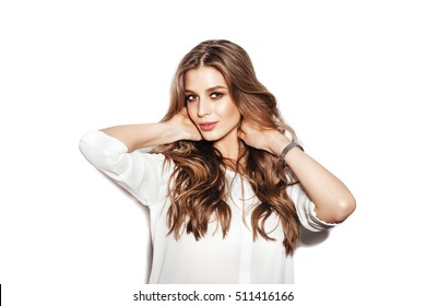 Beautiful girl with long wavy hair . Fair-haired model with curly hairstyle and fashionable makeup . Female model over white background not isolated