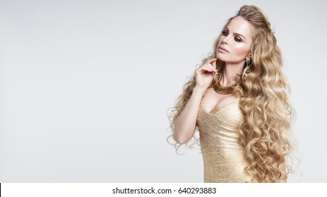 Beautiful girl with long wavy hair . Blonde with curly hairstyle. Volume, Hairstyle, Hairdressing Concept. High Quality. Jewelry