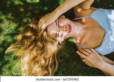 Beautiful girl with long white hair lies on green grass and smiles. Squint. A narrowed eye and a sly smile.