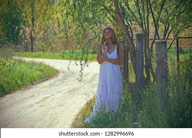 Beautiful girl in a long white sundress in nature