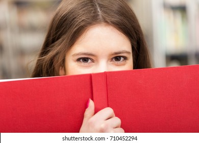 Beautiful girl looking from behind a book