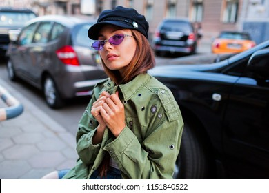Beautiful girl looking at camera. Close up portrait of fashionable lady in green jacket sitting near road  outdoor. Car parking  background.