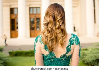 Beautiful girl looking forward in a amazing green dress before graduation