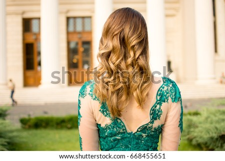 Beautiful girl looking forward in a amazing green dress before graduation
