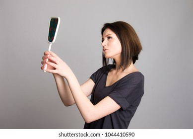 beautiful girl looking at her self in the mirror isolated on background studio