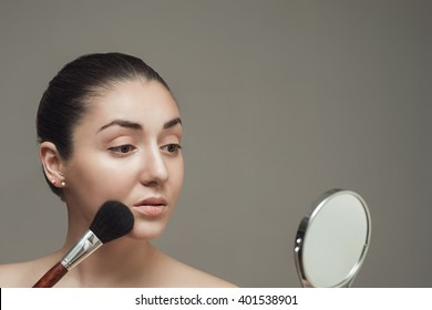 Beautiful girl looking in the mirror and applying cosmetic with a big brush. Girl gets blush on the cheekbones.