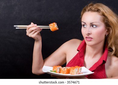 Beautiful girl looking to piece of sushi