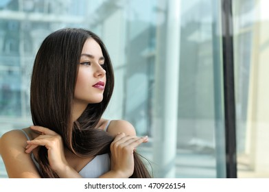 Beautiful girl looking to the side. She has long hair and well-groomed skin. Portrait on the background of modern architecture of metal and glass.
