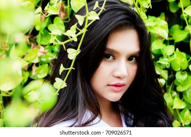 A beautiful girl looks so charming and attractive. She has a beautiful face.She has mixed race between Thai and English with beautiful green leaves fore ground and background.