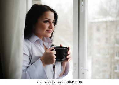 Beautiful girl looks out of window and holds a cup. Winter morning.
