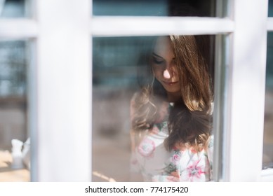 beautiful girl looks in the reflection of a window