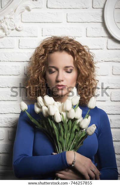 Beautiful girl with luxurious curly hair with her eyes closed holds a bouquet of white flowers