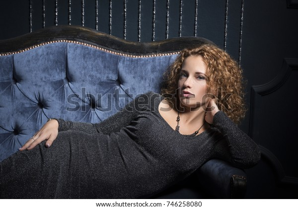 A beautiful girl with luxurious red curly hair lies on the couch and looks thoughtfully