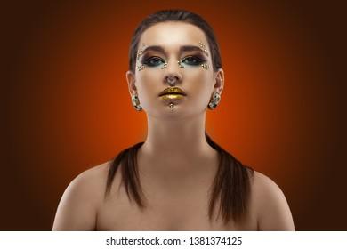 Beautiful girl. luxury shining makeup on the dark orange background