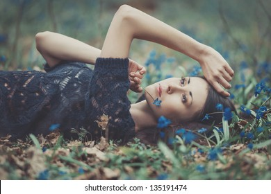 Beautiful girl lying among the snowdrops in the forest