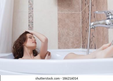 Beautiful girl lying in bathroom with eyes closed