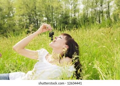 beautiful girl lying down of grass, eating black grapes. Copy space