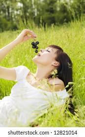 beautiful girl lying down of grass, eating black grapes