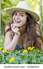 Beautiful girl lying in grass smiling with yellow flowers wearing a hat