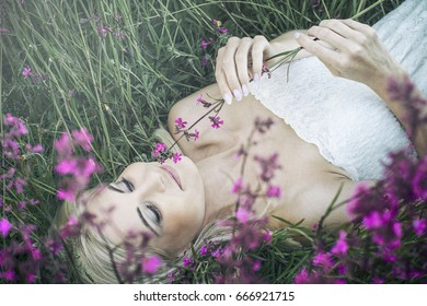 Beautiful girl lying in the ground in the meadow and smelling pink flower.
