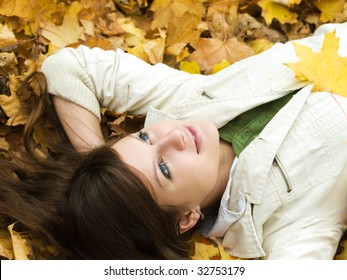beautiful girl lying on autumn maple leaves outdoors