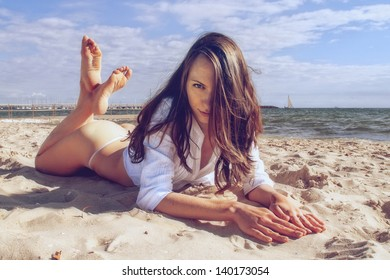 The beautiful girl is lying on the beach