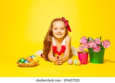 Beautiful girl lying on floor with tulips, eggs