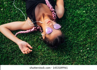 Beautiful girl lying on the grass summer green listen music earphones headphones hipster pink glasses pink braids european girl pink hair chilling phone sky