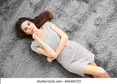 Beautiful girl lying on grey floor