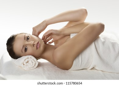beautiful girl lying on a table with withe towel on her body and under her head, she looks in to the lens and has both hands near the face