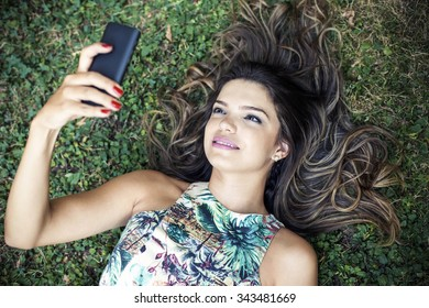 Beautiful girl lying in a park texting on a mobile phone