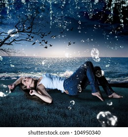 beautiful girl lying in the rain on a meadow in the evening