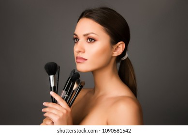 beautiful girl with make up brushes , perfect skin and make up woman concept