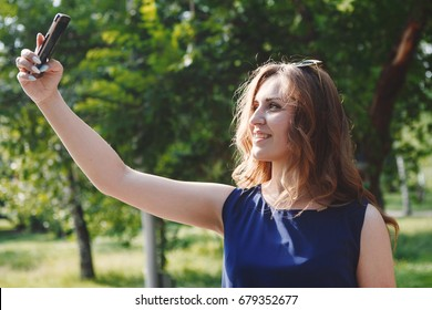 Beautiful girl makes selfie on smartphone outdoors in the Park on a Sunny summer day. Cute young woman photographing herself.