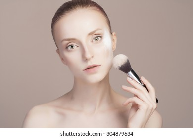 beautiful girl with make-up brush.beauty woman Applying Make-up.clean skin cosmetics.Young woman face with perfect skin