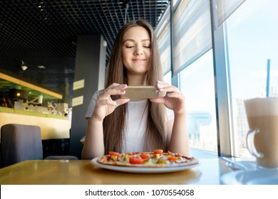 beautiful girl is making photo of food in cafe, latte on the table pizza, communication in social networks