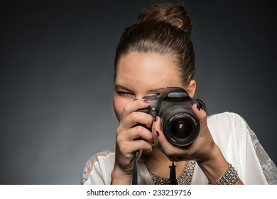 Beautiful girl making a picture with her new camera.