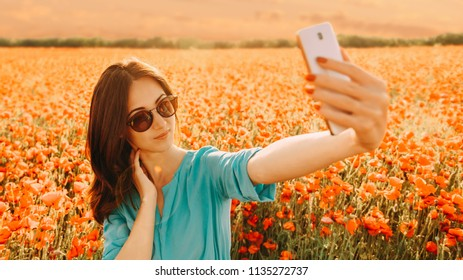 Beautiful girl making selfie with smartphone on background of poppies flower meadow in summer at sunset.
