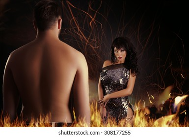 beautiful girl with a man stand afire and look to each other in eyes