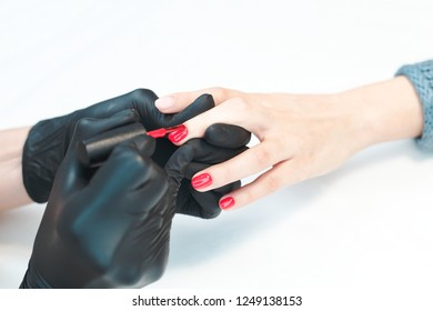 Beautiful girl manicurist doing manicure for woman in beauty salon. Colored manicure, nail painting in red color.