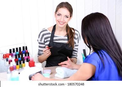 Beautiful girl manicurist doing manicure for woman in beauty salon