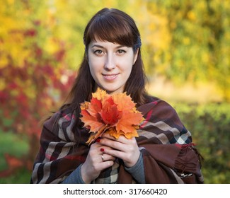 Beautiful girl with maple leaves in hands on nature background