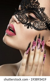 Beautiful girl in a mask with long fingernails. Portrait shot in the studio on a black background.